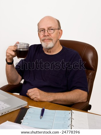 Senior man taking a coffee break while balancing his checkbook at his desk. - stock photo