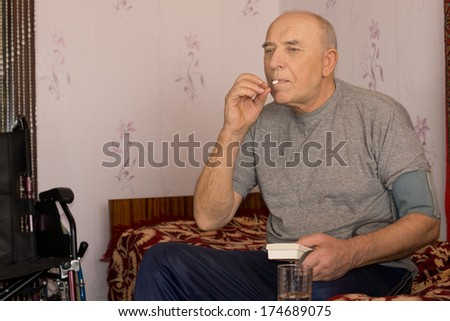 Senior man taking a tablet and his blood pressure using a pressure cuff as he sits at home in his living room alongside a wheelchair - stock photo