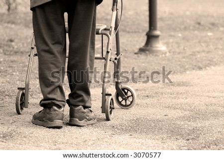 Senior man taking a walk in a park with the aid of a walking frame - stock photo