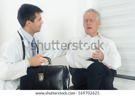 Senior man talking about pain and symptoms to young male doctor - stock photo