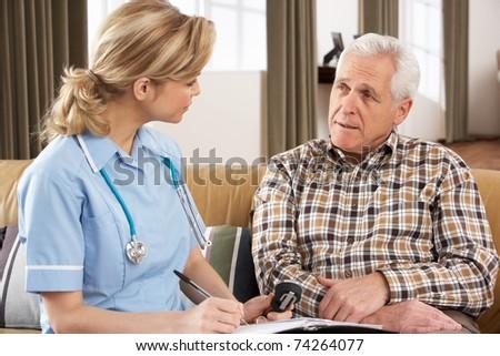 Senior Man Talking To Health Visitor At Home - stock photo