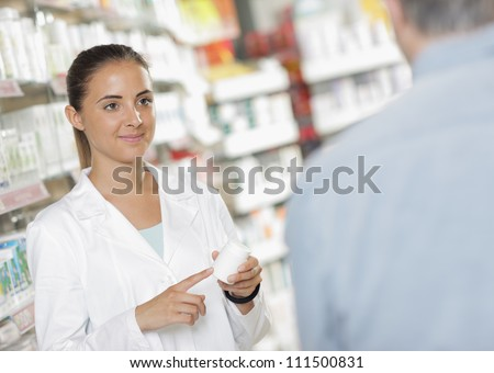 Senior man talking with woman pharmacist - stock photo
