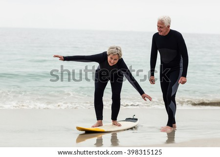 Senior man teaching woman to surf on beach - stock photo