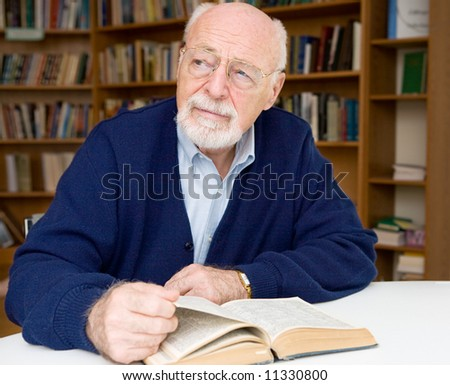 Senior man thinking about the book he is reading in the library. - stock photo