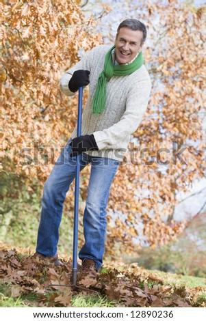 Senior man tidying autumn leaves in garden - stock photo