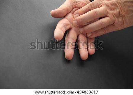 Senior man touches sore area of his hand. - stock photo