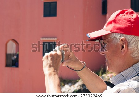 Senior man tourist taking photos using compact camera. - stock photo