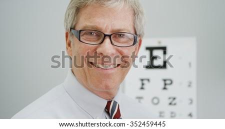 Senior man trying on new glasses - stock photo