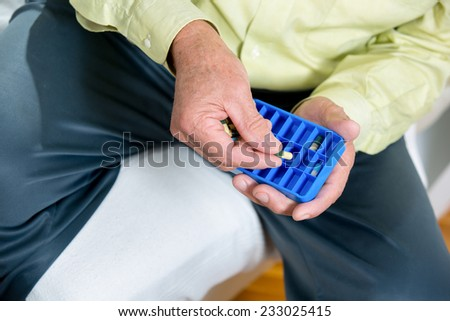 Senior man uses a pill organizer to prepare his medication for the week. - stock photo