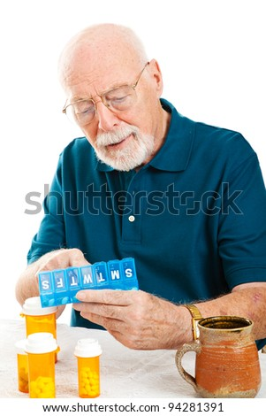 Senior man uses a pill organizer to prepare his medication for the week.  White background. - stock photo