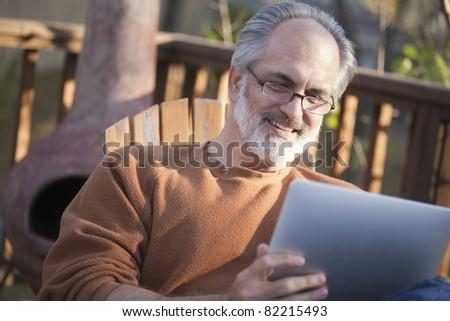 Senior man using a digital tablet outdoors - stock photo