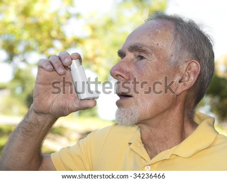 Senior man using asthma inhaler for allergies - stock photo