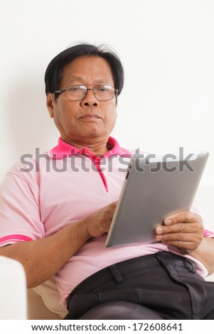 Senior man using digital tablet at home