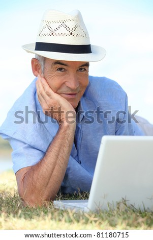 Senior man using his laptop lying on the grass