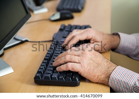 Senior Man Using Keyboard In Computer Class - stock photo