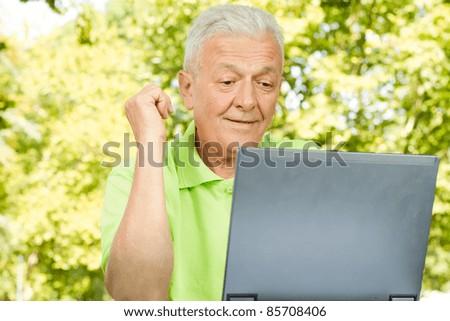 Senior man using laptop outdoors. - stock photo