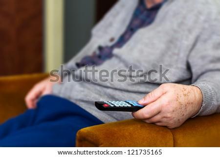 Senior man using remote control - stock photo