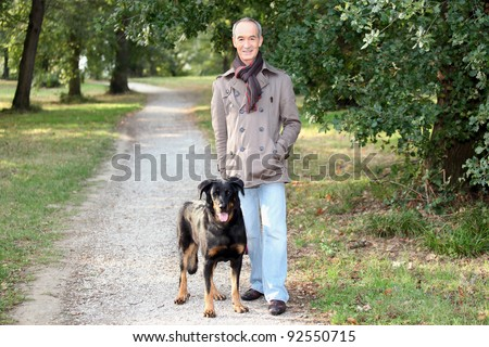 Senior man walking his dog in the woods - stock photo