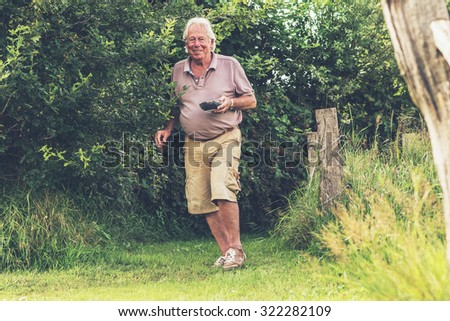 Senior man walking in garden with bowl fresh picked blackberries.