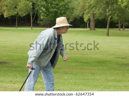 senior man walking in the park with a cane - stock photo