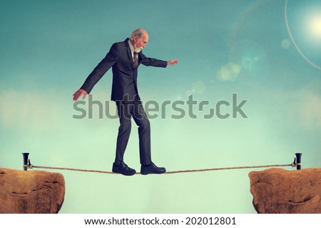senior man walking on a tightrope or highwire - stock photo