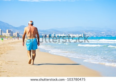 Senior man walking on the beach in Alicante, Spain