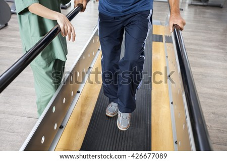 Senior Man Walking With Support Of Bars By Female Physiotherapis - stock photo