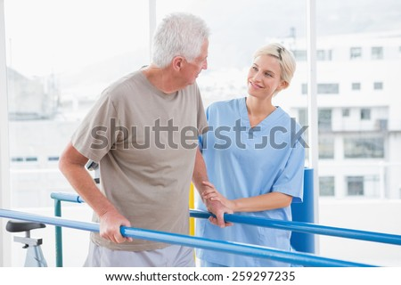 Senior man walking with therapist help in fitness studio - stock photo