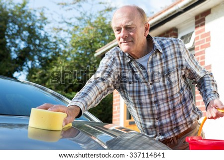 Senior Man Washing Car With Sponge