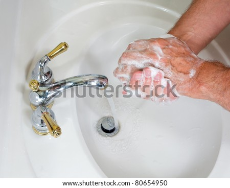 Senior man washing hands in modern sink with soap and lathering suds - stock photo