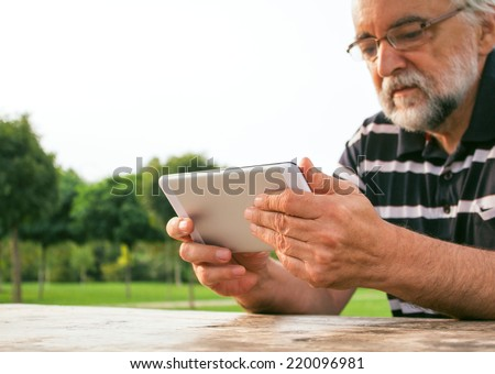 Senior man watching TV on his new tablet PC in the park. - stock photo