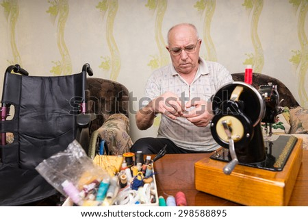 Senior Man Wearing Eyeglasses in Living Room with Wheelchair and Old Fashioned Sewing Machine and Supplies - stock photo