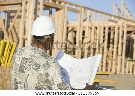 Senior man wearing hard hat with blueprint in front of incomplete house - stock photo
