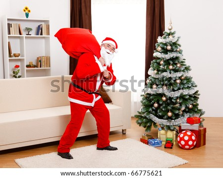 Senior man, wearing Santa Claus uniform, in front of Christmas Tree, walking away with full bag on the back