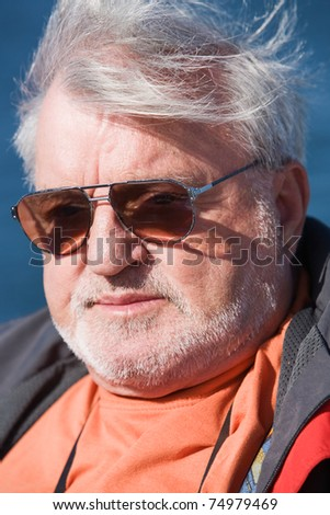 Senior man wearing sunglasses, wind, outdoors, close-up