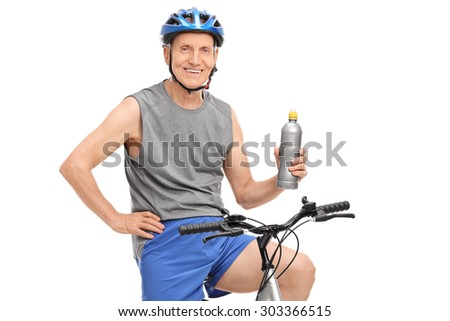 Senior man with a blue helmet holding a water bottle and posing seated on his bike isolated on white background - stock photo