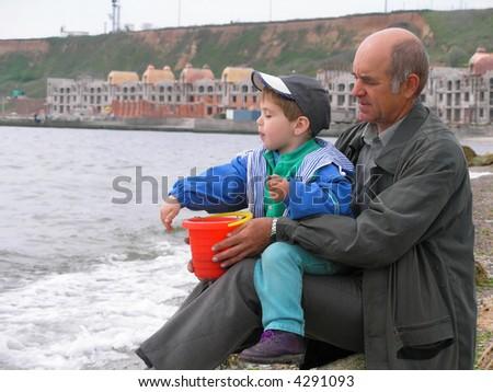 senior man with a grandson at sea - stock photo