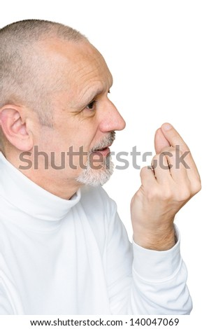 Senior man, with a smiling and ironic face, speaking of subtle, particular and precise argument, doing a gesture with the forefinger and the thumb. Isolated on white background.