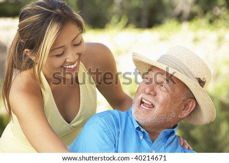 Senior Man With Adult Daughter In Garden - stock photo