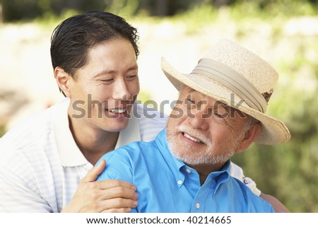 Senior Man With Adult Son In Garden - stock photo