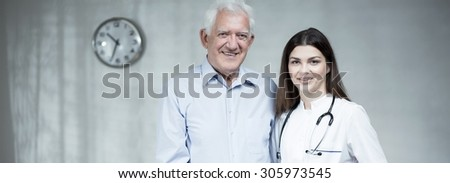 Senior man with attractive female doctor - panorama - stock photo