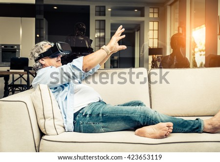 Senior man with augmented reality glasses lying down on the sofa - stock photo