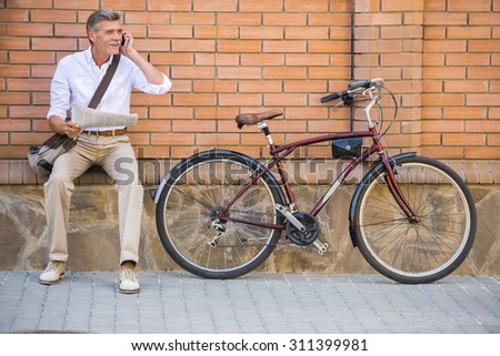 Senior man with bicycle and a newspaper is talking by phone sitting outdoors. - stock photo