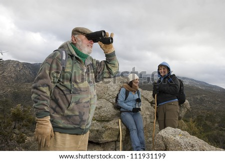 Senior man with binoculars on a hiking standing on a rock