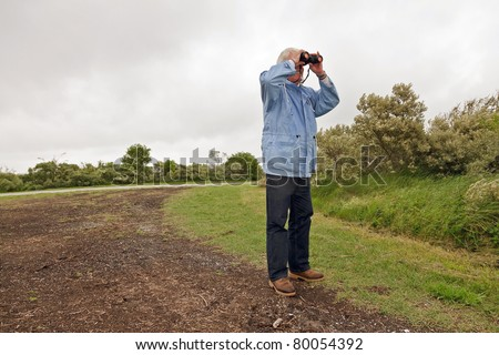 Senior man with blue jacket and binoculars outdoors on stormy day. - stock photo