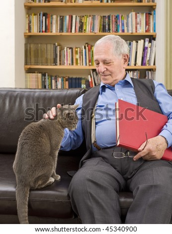 senior man with book at home caressing a cat on the sofa