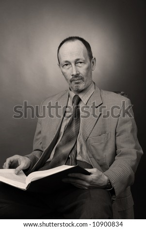 senior man with book, black and white, sepia - stock photo