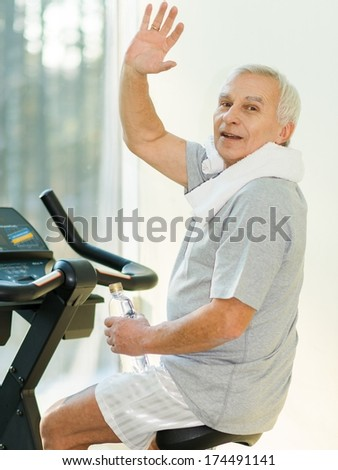 Senior man with bottle of water on a bike in a fitness club