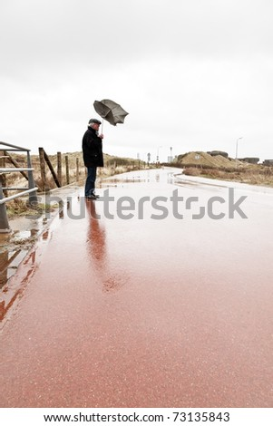 Senior man with broken umbrella by the wind standing on wet road.