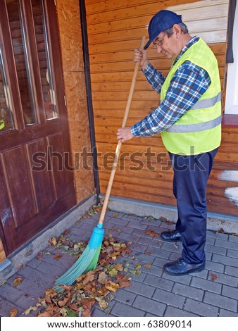 Senior man with broom sweeping fallen leaves - stock photo